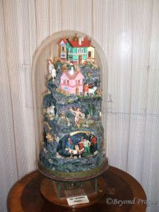Sculpted nativity under glass with a music box in the base.