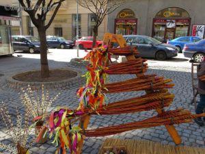 A rack of pomlázkas for sale on a street in Brno.